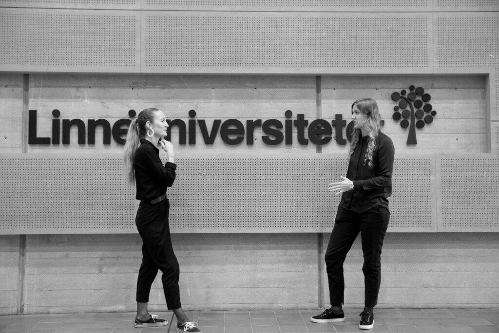 Ordförande och studiesocialt ansvarig samtalar framför en LNU skylt
